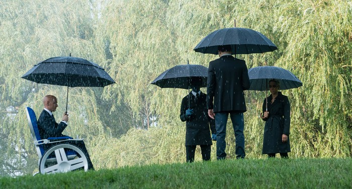 Four people dressed in black holding umbrellas in the rain