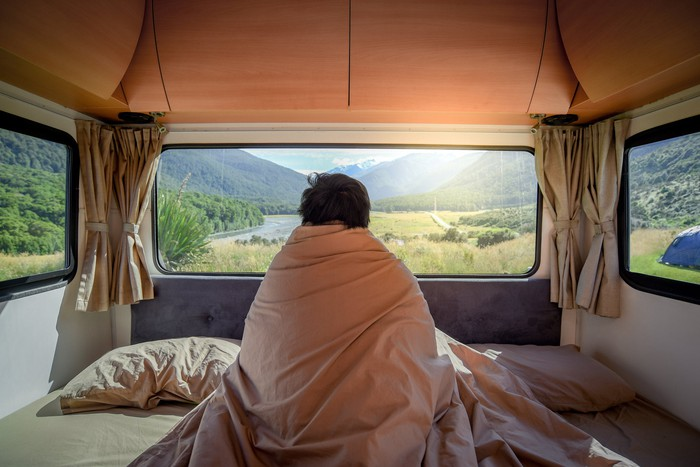 A person wrapped in a blanket and sitting on a bed looks out of an RV window