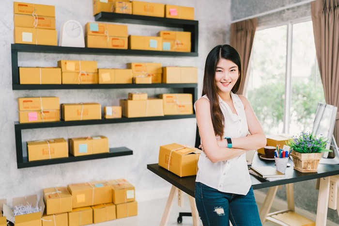Asian woman with boxes ready for shipping behind her.