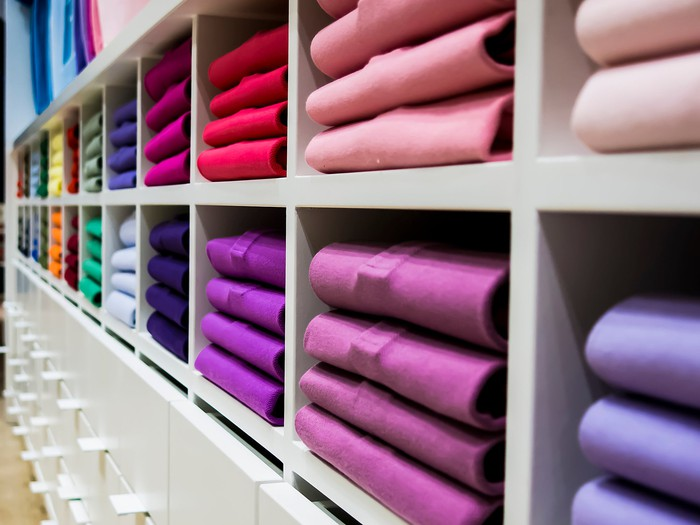 Stacks of brightly colored folded shirts on display in a clothing store