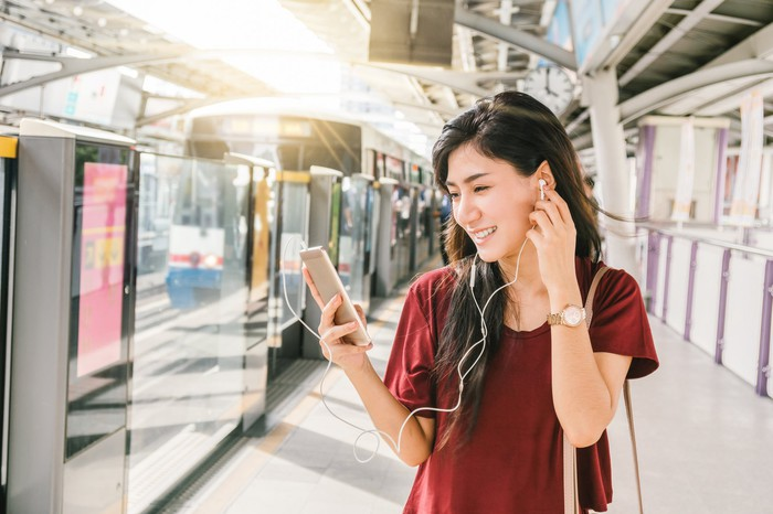 A young woman using a smartphone and wearing earphones.