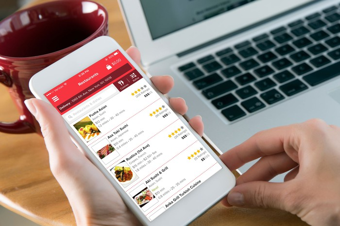 A pair of hands using the Grubhub app on a smartphone that's next to a laptop and empty mug.