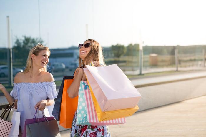 Two women carry shopping bags.