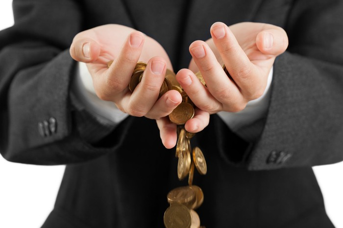A man in a business suit's hands, with coins falling through his fingers.
