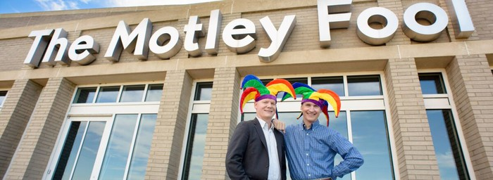 Tom and David Gardner, wearing jester caps, and standing in front of The Motley Fool HQ.