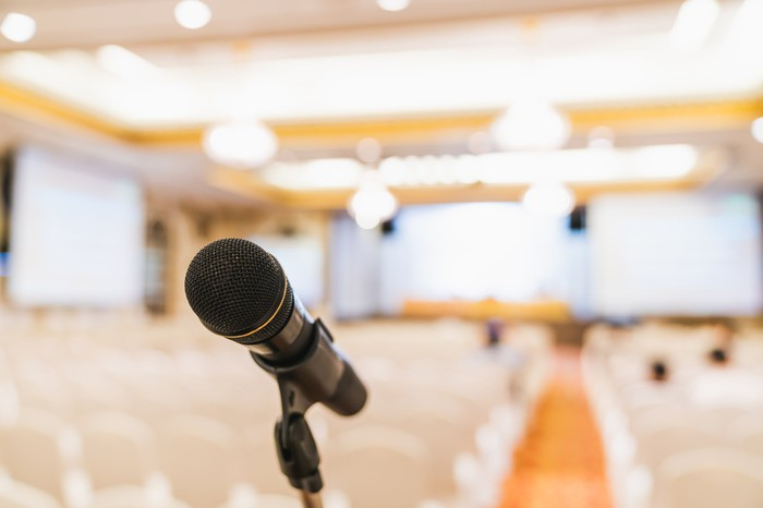 A microphone on a stand in front of an empty conference room.