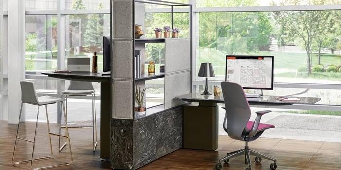 A contemporary open-plan office space facing a corporate garden.