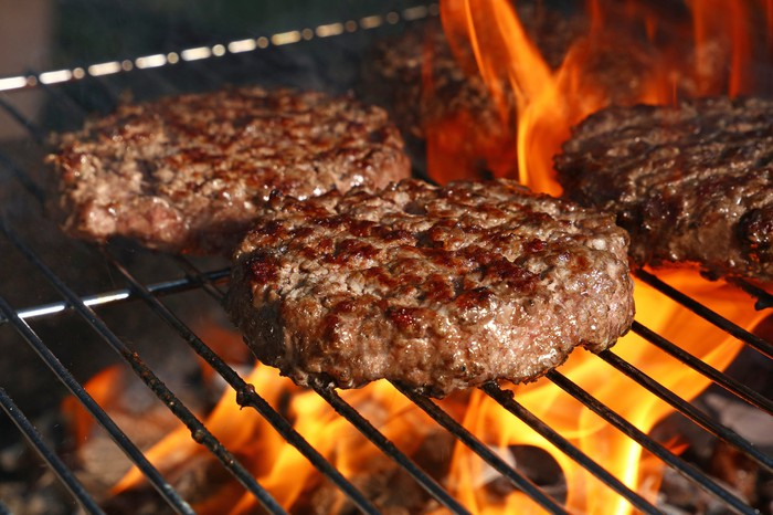 Several burger patties grilling over an open fire.