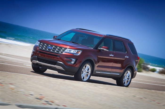 A dark red 2016 Ford Explorer, a midsize SUV, on a beach road.