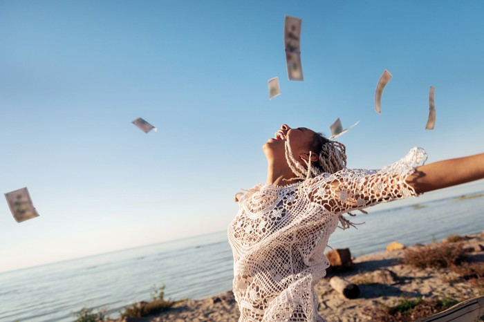 Woman at beach throwing money into the air.