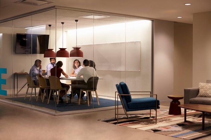 A business team holds a conference in a contemporary glass-walled conference room.