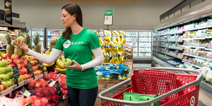 A woman wearing a Shipt shirt, picking out fruit in Target