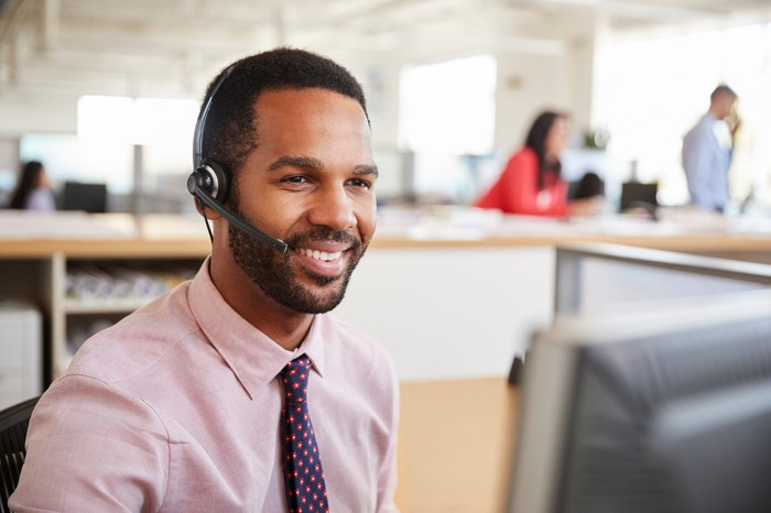Smiling man wearing headset, and sitting in front of computer in an office.