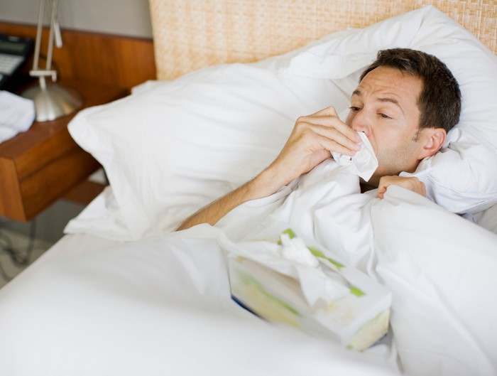 Man lying in bed, wiping his nose