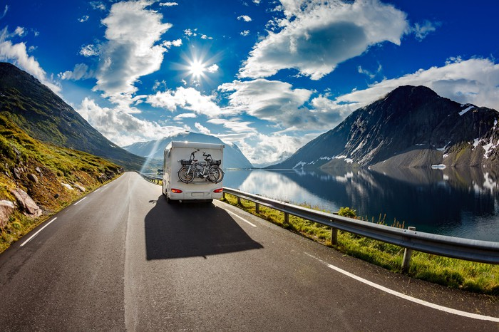 RV driving on a highway, with a lake and mountains in the background