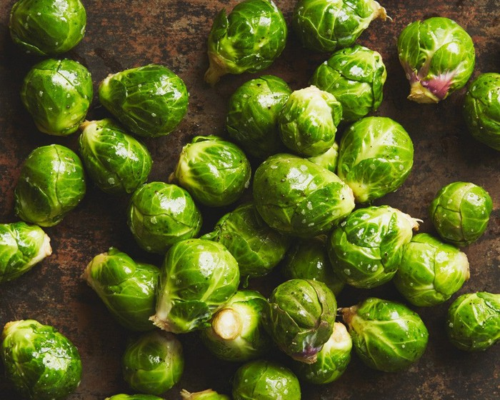 Several bright-green brussels sprouts in a pan.