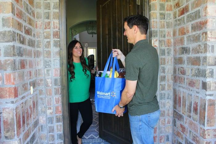 A Man Holding A Walmart Bag Of Groceries Handing It To A Woman Inside A Doorway