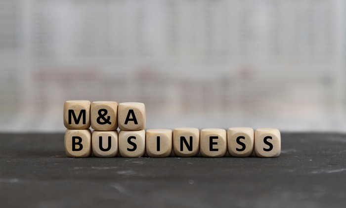 M&A Business spelled out with wooden blocks.