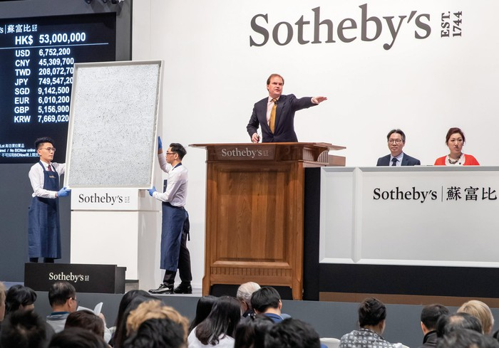Person at podium pointing next to an artwork, with Sotheby's logo on back wall.