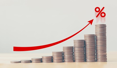 Rising stacks of coins with a red arrow pointing to a percentage symbol.