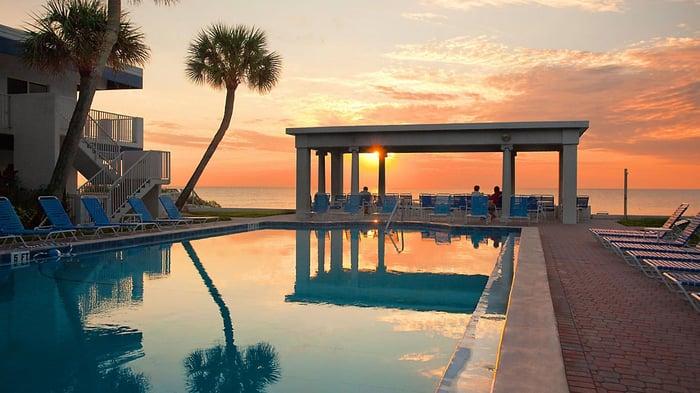 A beachside hotel pool reflecting a sunset