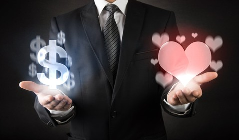 A man in a suit with money symbols in one hand and hearts in the other.