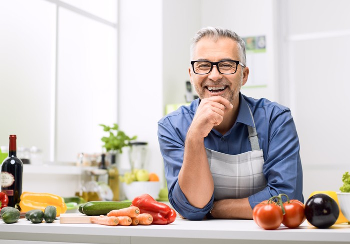 Older man in apron smiling, leaning against counter with various vegetables on it