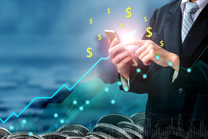 Businessman with calculator surrounded by dollar signs and a line chart going up