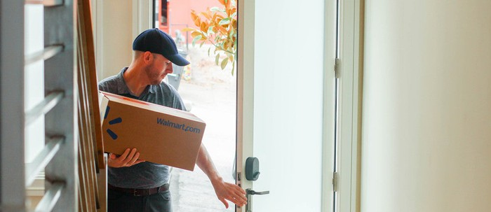 A Walmart employee delivers a box into someone's home.