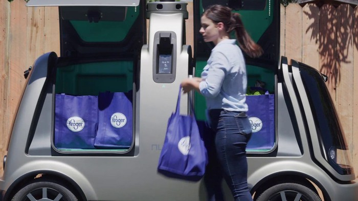A woman removes Kroger groceries from a self-driving vehicle.