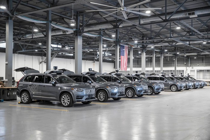 A row of Volvo SUVs in a warehouse.