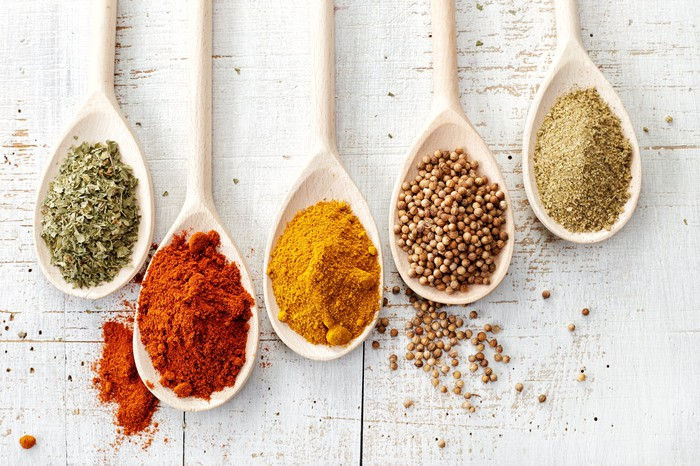 Five spoons filled with different spices.