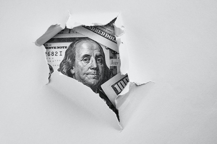 A ripped hole in a white piece of paper revealing a $100 bill hidden underneath.
