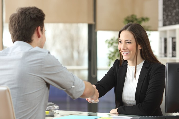 Woman in commerce suit shaking fingers with man across the desk