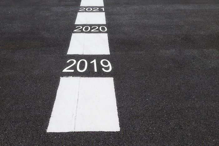 White rectangles and years 2019 through 2021 painted on a road surface.