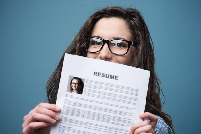 Smiling woman holding up her resume.