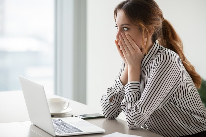 Woman at laptop with shocked expression holding her face