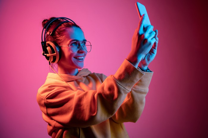 A young woman in glasses and headphones takes a selfie.