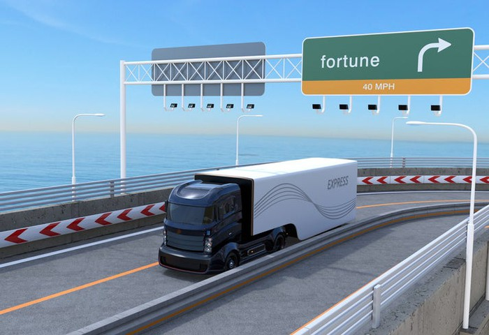 Artist's rendering of an autonomous tractor-trailer traveling on a highway adjacent to a body of water with blue sky in background.