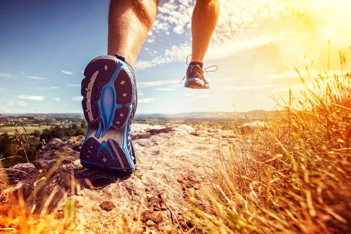A runner jogs on an outdoor trail.