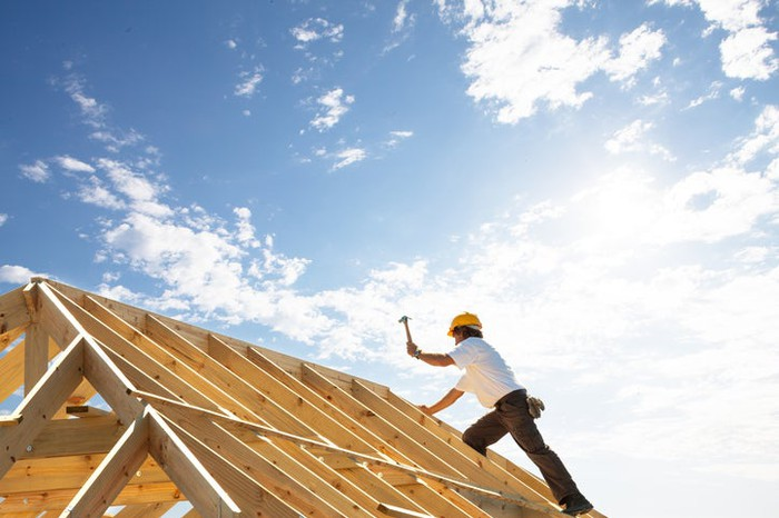 A worker framing a roof on a house.