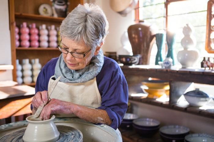 Gray-haired person making a clay pot in a shop with many materials.