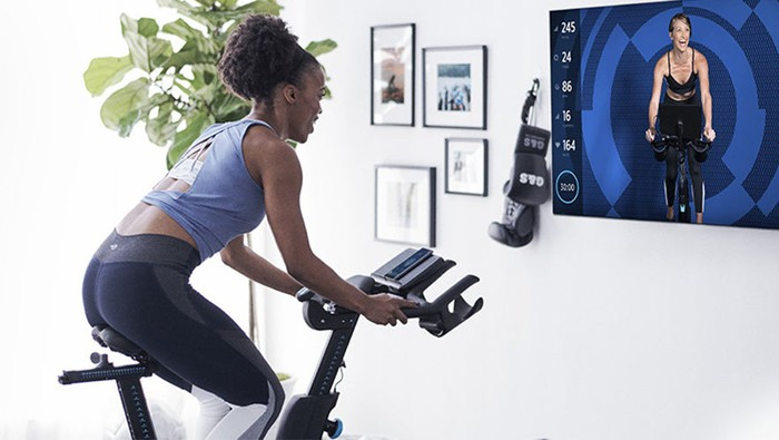 Woman on a connected stationary bike watching a spinning instructor on a television on the wall..