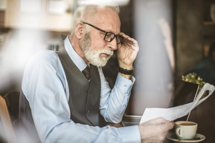 Professionally dressed older man reading a document
