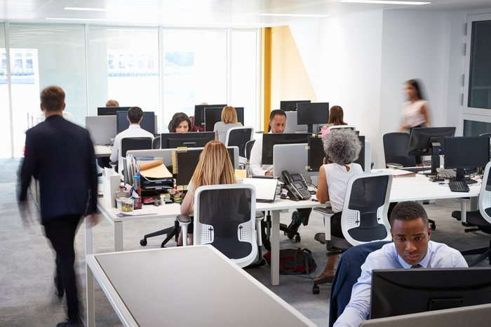 Office with rows of people at desks.