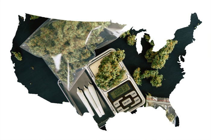 A black silhouette of a continental map of the United States, partially filled in with cannabis baggies, rolled joints, and a scale.