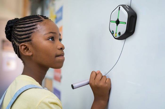 Young female student drawing a line for iRobot's Root coding robot to follow on a whiteboard.