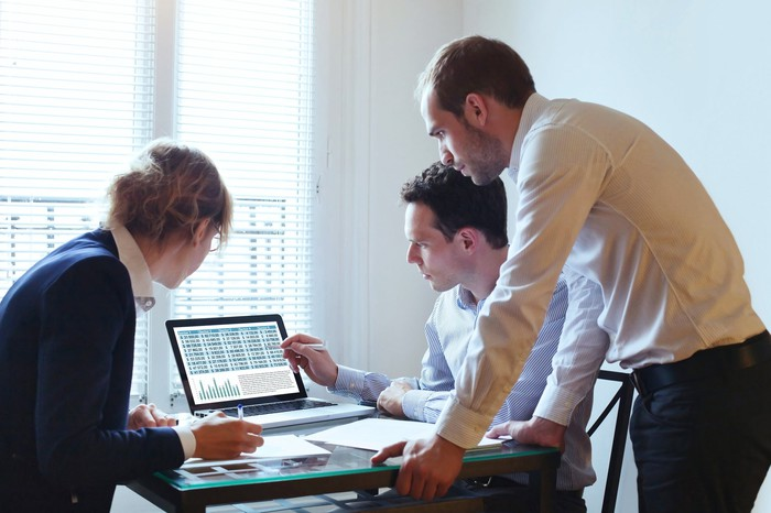 A group of three office workers are gathered around a computer, looking at a chart.