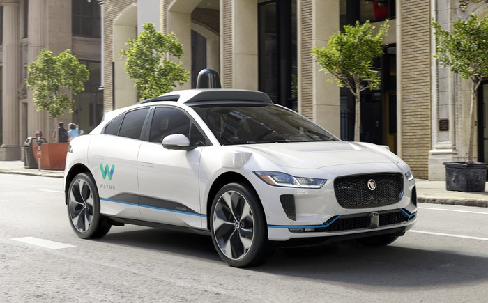 A white Jaguar I-Pace SUV, with self-driving sensor hardware and Waymo logos, on a city street.
