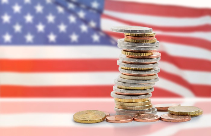 A stack of coins sitting in front of an American flag.